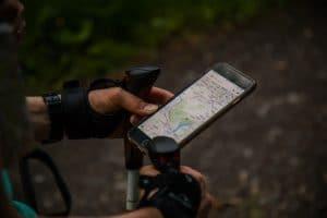 Mężczyzna z kijami do nordic walking trzyma telefon z GPS