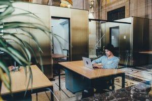 Mężczyzna pracujący na laptopie w jakiejś instytucji
