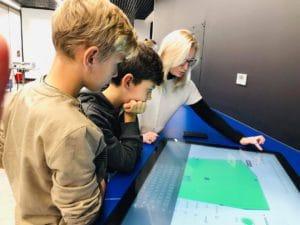 Dzieci grają w grę na ekranie interaktywnym