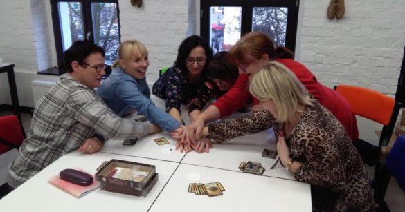 Bibliotekarki przy stole grają w gry planszowe