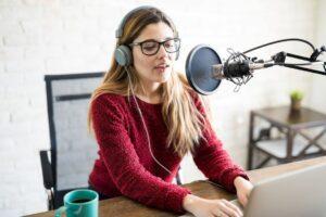 Kobieta ze słuchawkami przy komputerze mówi do mikrofonu